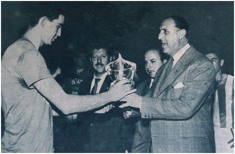 El directivo Luis De Carlos entrega al capitán madridista, Jiménez, el trofeo en disputa.