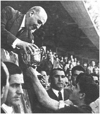 El Jefe del Estado, Francisco Franco, entrega al capitán rojiblanco Collar el trofeo obtenido.