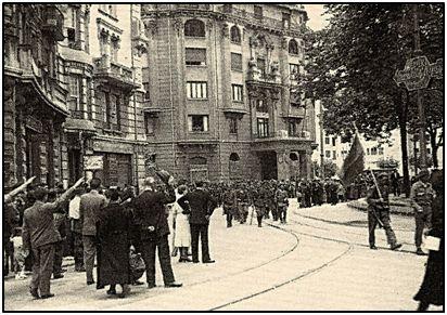 Entrada victoriosa en Bilbao de las Brigadas de Navarra, vitoreadas por sus partidarios y entre brazos en alto que sustituían al anterior saludo con el puño bien cerrado.